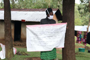 The Water Project: Lutali Community, Lukoye Spring -  The Faciliator Holding Up The Chart