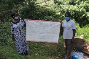 The Water Project: Shirakala Community, Ambani Spring -  Two Members With The Chart At The Spring