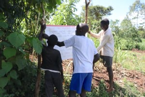 The Water Project: Chegulo Community, Yeni Spring -  Installing The Pillars To Support The Reminder Chart