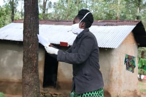 The Water Project: Lutali Community, Lukoye Spring -  The Facilitator Demonstrating How To Make A Mask