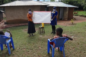 The Water Project: Ematetie Community, Weku Spring -  The Facilitators Holding Up The Reminder Chart