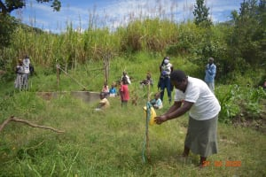 The Water Project: Bukhanga Community, Indangasi Spring -  Demonstrating Leaky Tin Use
