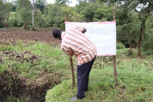 The Water Project: Malava Community, Ndevera Spring -  The Water Committee Chair Installs The Reminder Chart At The Spring