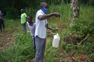 The Water Project: Emukoyani Community, Ombalasi Spring -  Trainer Protus Sets Up The Leaky Tin At The Spring