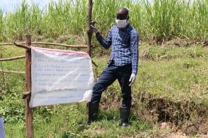 The Water Project: Sambaka Community, Sambaka Spring -  Trainer Erick Installing The Poster At The Spring