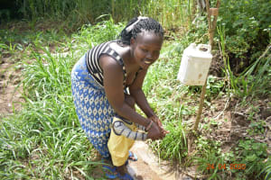 The Water Project: Emukoyani Community, Ombalasi Spring -  Helping Her Child Wash Hands