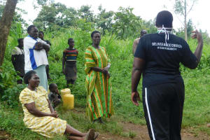 The Water Project: Mungakha Community, Nyanje Spring -  Community Members Listen To Team Leader Emmah