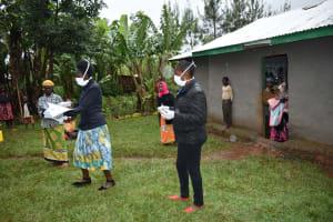 The Water Project: Namarambi Community, Iddi Spring -  Facilitators With Protective Gear Conducting Training