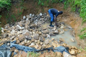 The Water Project: Shikangania Community, Abungana Spring -  Backfilling With Stones