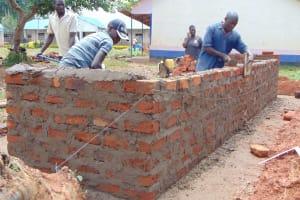 The Water Project: Jinjini Friends Primary School -  Latrine Brick Walling