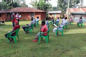The Water Project: Shirakala Community, Ambani Spring -  Community Members Listening