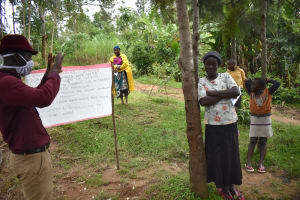 The Water Project: Bukhakunga Community, Ngovilo Spring -  Facilitator Reviewing Prevention Reminder Chart