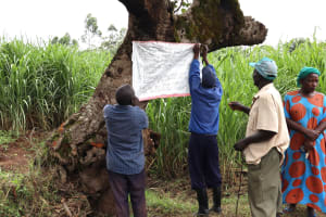 The Water Project: Shitoto Community, William Manga Spring -  Affixing Prevention Reminder Chart