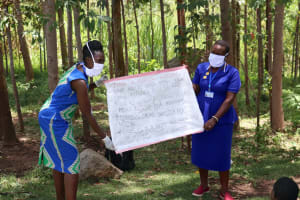 The Water Project: Shirugu Community, Shapaya Mavonga Spring -  Trainers Shigali And Maruti Hold Chart Of Prevention Reminders