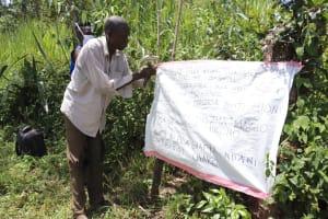 The Water Project: Shirugu Community, Shapaya Mavonga Spring -  Pinning Reminder Chart Near Spring