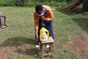 The Water Project: Ematetie Community, Weku Spring -  Trainer Amulavu Demonstrating Handwashing