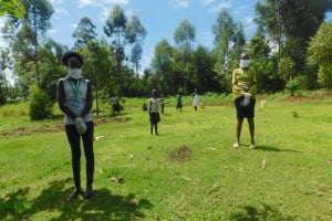 The Water Project: Ataku Community, Ngache Spring -  Fotf Staff Demonstrate Social Distancing
