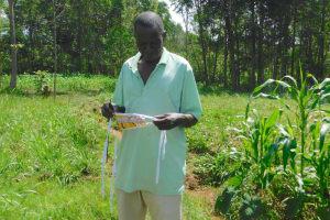 The Water Project: Sichinji Community, Kubai Spring -  Mr Kubai Shows Is Homemade Mask