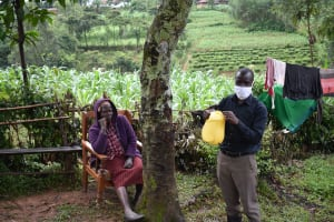 The Water Project: Maganyi Community, Bebei Spring -  Sir Erick Holding Up The Leaky Tin