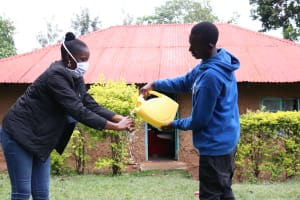 The Water Project: Malava Community, Ndevera Spring -  Assisintg The Facilitator To Rinse Her Hands