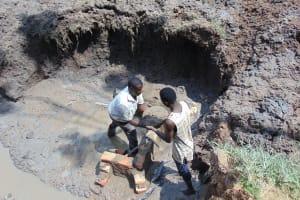 The Water Project: Shikangania Community, Abungana Spring -  Teamwork Passing Bowl Of Concrete