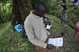 The Water Project: Ingavira Community, Laban Mwanzo Spring -  Reading An Informational Pamphlet