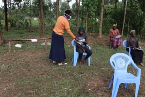 The Water Project: Ematetie Community, Weku Spring -  Trainer Rose Distributing Pamphlets