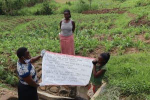 The Water Project: Shitoto Community, Abraham Spring -  Installing The Prevention Reminder Chart