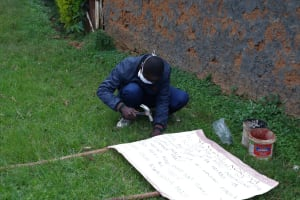 The Water Project: Itukhula Community, Lipala Spring -  Trainer Simidi Nailing The Chart Onto The Poles