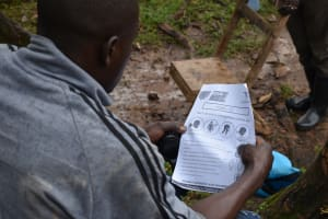 The Water Project: Maganyi Community, Bebei Spring -  Using Handouts With Covid Information At The Training