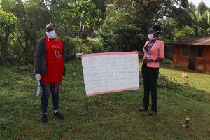 The Water Project: Shirakala Community, Ambani Spring -  The Facilitators Holding Up The Reminder Chart