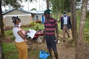 The Water Project: Bukhakunga Community, Ngovilo Spring -  Trainer Kamau Distributing The Manuals
