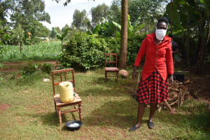 The Water Project: Ibinzo Community, Lucia Spring -  Covid Facilitator Wearing Protective Gear Next To Handwashing Station