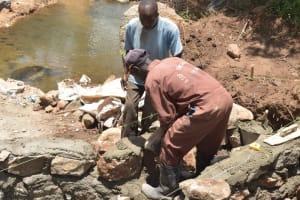 The Water Project: Kasioni Community B -  Hauling Rocks