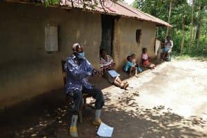 The Water Project: Masera Community, Ernest Mumbo Spring -  A Community Member Illustrating Handwashing