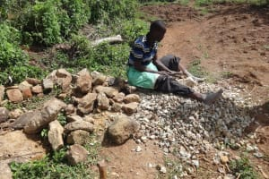 The Water Project: Mahira Community, Jairus Mwera Spring -  A Community Mamber Breaks Stones Into Gravel
