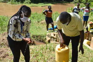 The Water Project: Lwenya Community, Warosi Spring -  A Community Member Helped Her Out A Bit