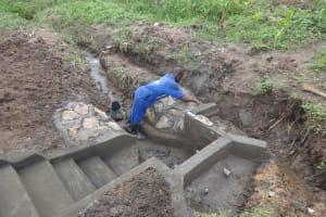 The Water Project: Mahira Community, Jairus Mwera Spring -  Cementing The Stone Pitching