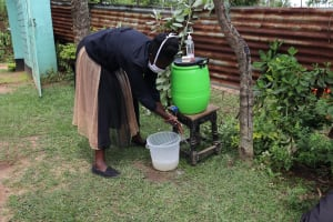 The Water Project: Masera Community, Salim Hassan Spring -  The Facilitator Cleaning Her Hands In Demonstration