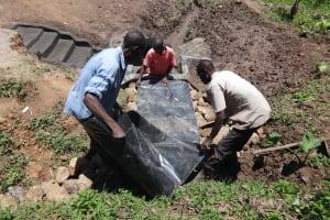 The Water Project: Mahira Community, Jairus Mwera Spring -  Backfill With Plastic Tarp