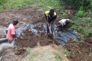 The Water Project: Mahira Community, Jairus Mwera Spring -  Soil Backfilling Process