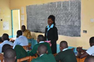 The Water Project: Ebubole UPC Secondary School -  Sanitation Teacher Emphasizing Importance Of Wash