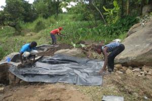 The Water Project: Mahira Community, Kusimba Spring -  Backfilling With Tarp Layer