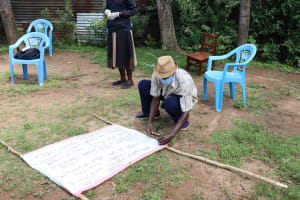 The Water Project: Masera Community, Salim Hassan Spring -  A Coomunity Member Helping Nail The Chart To The Support Poles