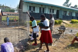 The Water Project: Ebubole UPC Secondary School -  Team Leader Emmah Measures The Wire With Help From Attaches
