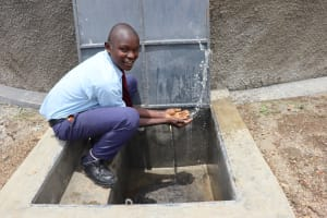 The Water Project: Friends School Vashele Secondary -  Moses Happily Splashing Water From Finished Water Tank