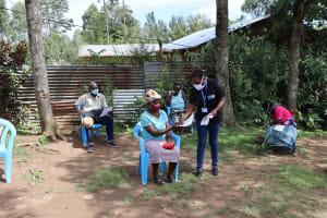 The Water Project: Masera Community, Salim Hassan Spring -  Mrs Afandi Distributing The Manuals