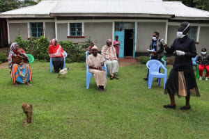 The Water Project: Shitungu Community, Hessein Spring -  Madam Shigali With Protective Gear Condicting Training