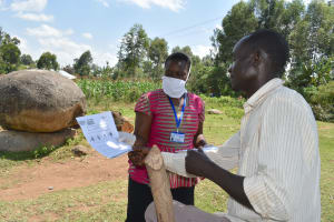 The Water Project: Musango Community, Jared Lukoko Spring -  Facilitator Going Through A Handout With A Community Health Worker