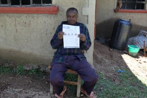 The Water Project: Muraka Community, Peter Itevete Spring -  A Community Member Holds A Handout Translated Into His Native Language